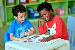 Boys in kindergarten Read magazines in an international school library.teacher ,education, kid and primary school concept .