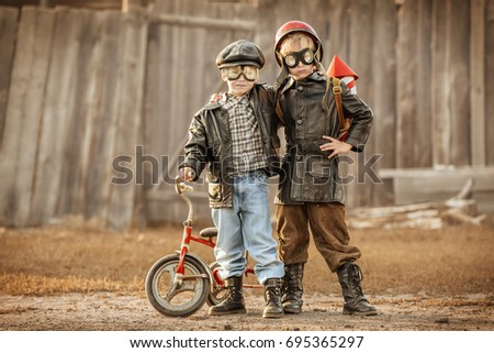 Boys in the image of a rider and a rocket-man play in the backyard of the house #695365297