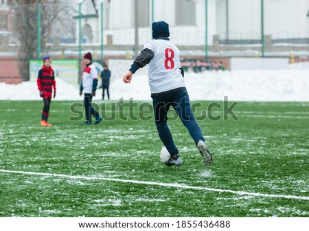 Photo of  Boys in white sportswear running on soccer field with snow on background. Young footballers dribble and kick football ball in game. Training, active lifestyle, sport, children winter activity