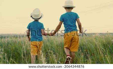Boys kids playing in park in summer at sunset. Children, friends, travel to summer field holding hands. Childrens dreams and fantasies in nature. Carefree children play together outdoors. Happy family
