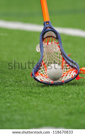 Boys lacrosse stick scoops the ball up off the field for control of the ball and game.