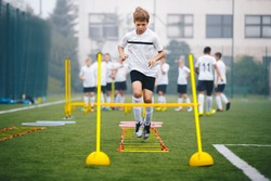 Boys on Agility Training on School Soccer Pitch. Athlete Soccer Player In Training. Young Boy Running Through Ladder and Skipping. Agility Ladder Drills and Ladder Exercises