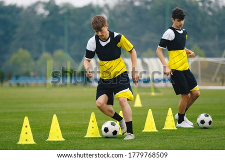 Photo of  Boys on soccer football training. Young players dribble ball between training cones. Players on football practice session. Soccer summer training camp
