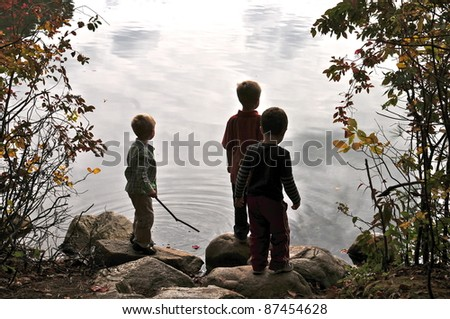 Boys on the shore of Walden Pond watch the cloud reflection in the water