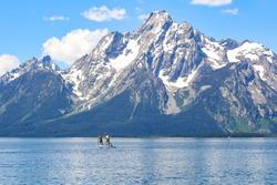 Boys paddle boarding on Jackson Lake in Grand Teton National Park, Wyoming, USA