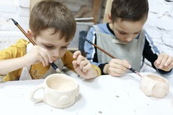 Boys paint clay pots in pottery workshop