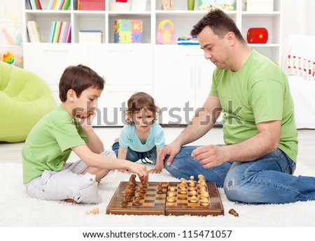 Boys playing chess with their father in the kids room - focus on smaller child