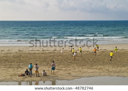 Boys playing football with low tide