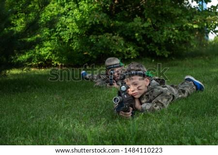 Boys playing in lasertag shooting game, boy with a gun, war simulation.