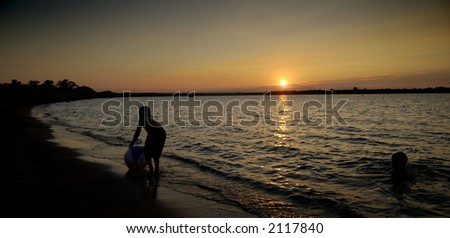 Boys playing on a beach in the early evening