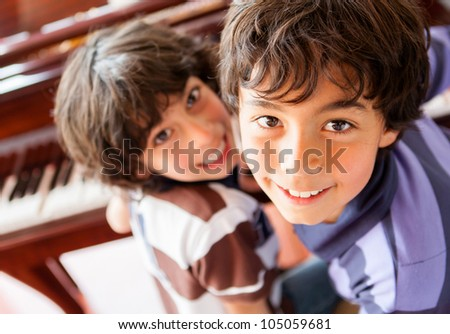 Boys playing the piano at home and smiling