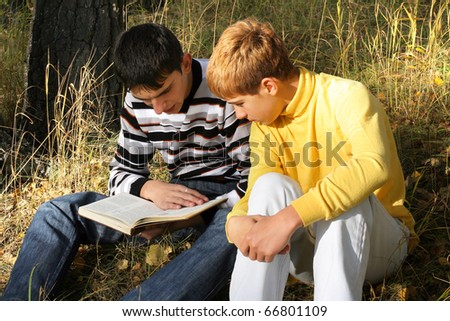 boys sit in autumn forest with a book