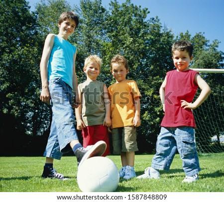Photo of Boys standing around soccer ball