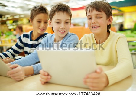 Boys surfing the net on their touchpads in cafe  - stock photo