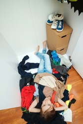 Boys untidy home room interior. Lazy kid lying among scattered clothes inside messy room. Home chores housework. Mess in open wardrobe. Untidy clutter clothing closet.