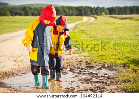 Boys walking in a mud puddle