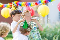Boys wearing birthday hats playing outdoors, letting soap bubbles