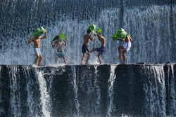 Boys were having fun by playing water in an artificial dam on the Tukad Unda dam, Bali, Indonesia. Bali island is a popular tourist destination in the world. Happiness, joyfull, friendship concept