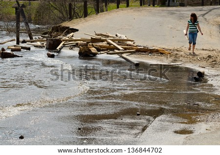 BRACEBRIDGE ONTARIO - APRIL 28, 2013: Young woman surveying the damage caused by worst flood in hundred years in Bracebridge Bay Park  on April 28, 2013 in Bracebridge, Ontario, Canada.