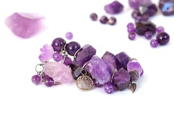 Bracelet made of natural amethyst beads and untreated stones, connected by rings and pendants. Amethyst minerals are washed out in the background. Purple lilac amethyst isolated on white background
