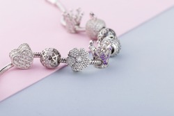 Bracelet with silver charm beads with gems. Flower, crown, ball, heart beads.  Product concept for jeweler