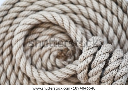 Braided thick rope tied in a skein. Hemp rope for decoration and design. Background from fishing rope.