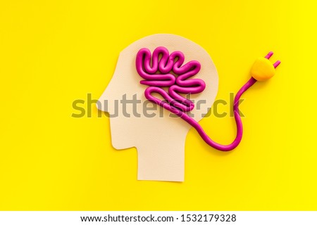 Brain charging and mental rest. Plug and cable leads to plastiline meanders on yellow background