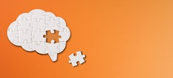 Brain shaped white jigsaw puzzle with copy space on orange background, a missing piece of the brain puzzle, mental health and problems with memory