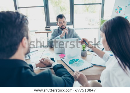 Brainstorm concept. Group of three business partners are discussing the project at nice modern office. They are all serious and concentrated. Boss is asking subordinates about report, rear view