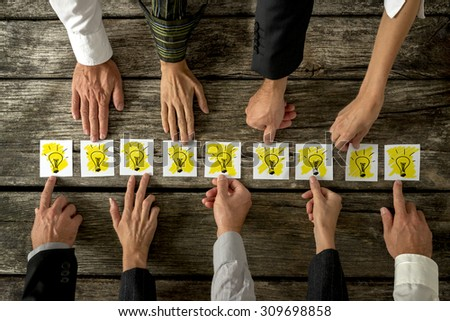 Brainstorming and teamwork concept with a group of diverse business people each holding out a card with a shining light bulb arranged in a row conceptual of ideas, inspiration and innovation.