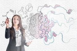 Brainstorming concept with businesswoman painting by pen illustration of human brain on glass screen at light brick wall background