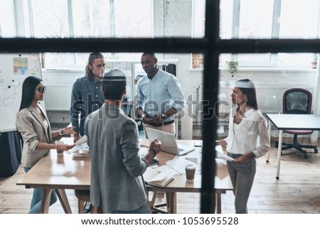 Brainstorming for a new project. Top view of young modern people in smart casual wear discussing business while standing behind the glass wall in the board room