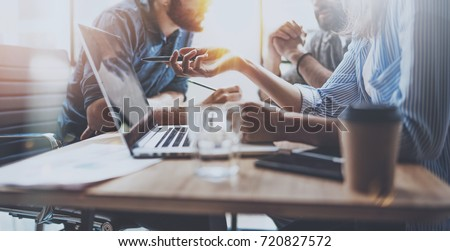 Brainstorming process at sunny office.Young coworkers work together modern office studio.Young people making conversation at wooden table.Horizontal wide.Blurred background #720827572