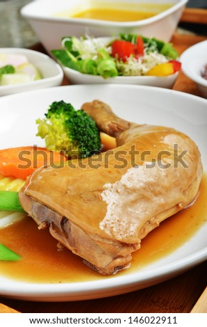 Braised chicken leg with vegetables on the plate