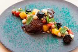 Braised veal cheek with fruits and berries on slate plate