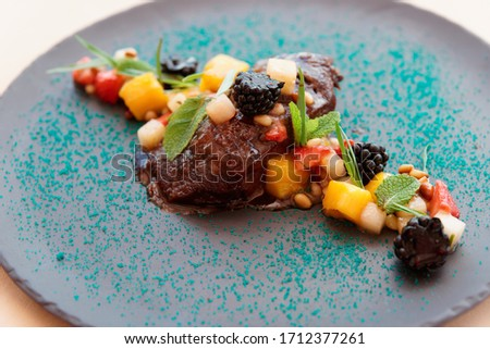 Braised veal cheek with fruits and berries on slate plate Photo stock ©