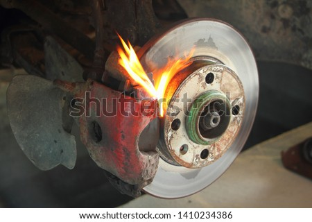 Brake caliper, pads and disk on flame on front suspension elements background - dangerous of overheating car brakes #1410234386