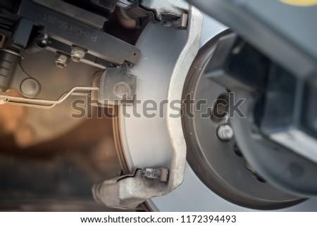 Brake disc grinding machine - Vehicle brake-disc turning machine. Automobile disc brake system repair in garage. #1172394493