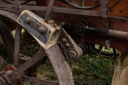 Brake of a historic agricultural vehicle, a threshing machine consisting of a wooden brake pad, steel wheel and steel actuating linkage