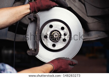 Brake repair. Mechanic changing brake disc