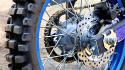 Brake system and rear wheel hub motocross motorcycle. Blue rims with tires and spokes. Select the content and focus.