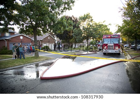 BRAMPTON, ONTARIO -  JULY 20 2012 - Crowd gathers to watch a house fire burning at 20 Esker Drive in Brampton Ontario on July 20, 2012
