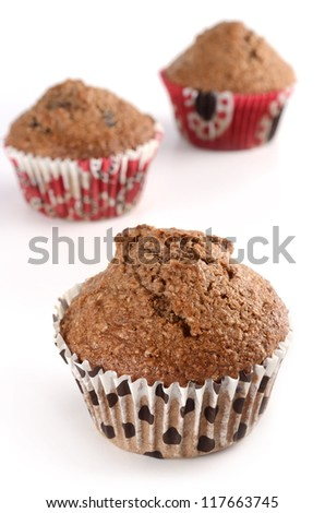 Bran muffins in decorative cups on white background in vertical format - stock photo