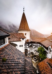 Bran, Romania - 30 November 2019: Bran Castle roofs on misty mountains background