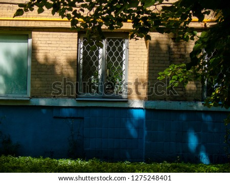 Branch and leaves in front of building. Sunlight spots on brick wall. Window with lattice on brick home. Simple decor on  architecture. Courtyard garden of living house. Spring or summer season.