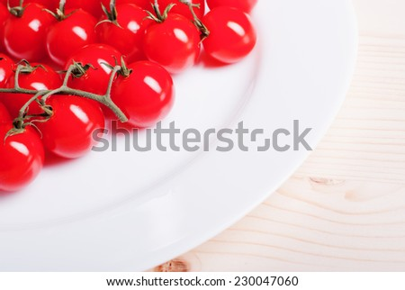 branch of cherry tomatoes in a white plate on a light wooden table top view and side view
