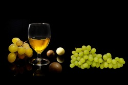 Branch of Fresh Green Grapes With a Glass of Wine and Chocolate   - Isolated on a black Background