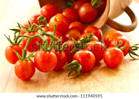branch of red ripe cherry tomatoes on a wooden board