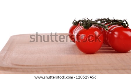 branch of tomatoes on cutting board