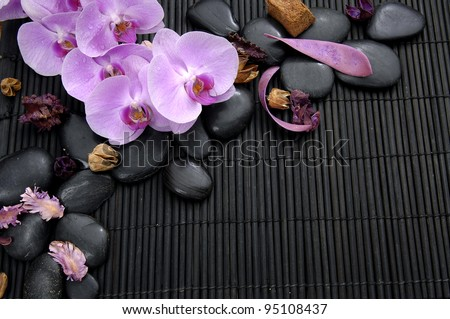 Branch pink orchid with stones and petals on bamboo mat